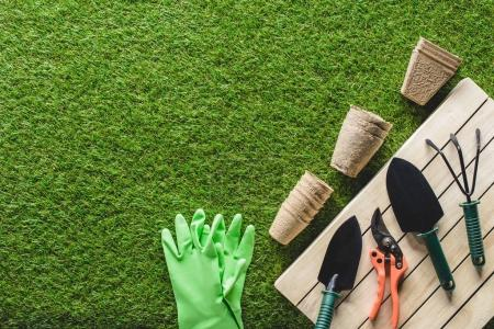 top view of protective gloves, flower pots and gardening tools on grass