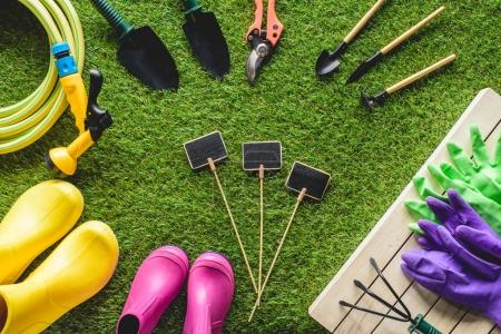 Photo for Top view of empty blackboards surrounded by rubber boots, gardening equipment and protective gloves on grass - Royalty Free Image