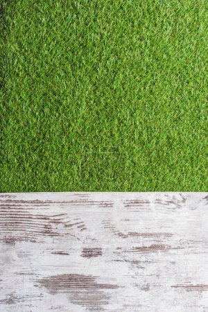 top view of green lawn and wooden planks background