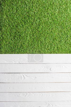 top view of green lawn and white wooden planks background