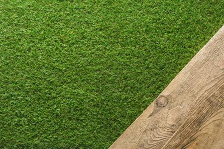 top view of green lawn and wooden plank background