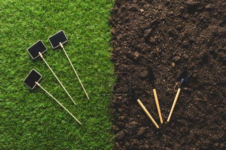 top view of empty blackboards on grass and gardening tools on soil