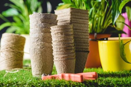 closeup shot of stacks of flower pots and secateurs on grass