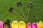 vue de dessus de tableaux vides, bottes en caoutchouc, gants de protection, outils de pot et jardinage fleur