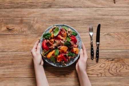 cropped shot of hands holding plate with gourmet salad with mussels and vegetables