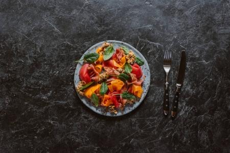 top view of gourmet salad with mussels, vegetables and jamon on black marble surface