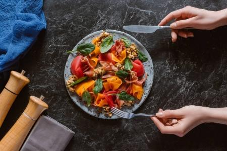 partial top view of person eating delicious salad with mussels, vegetables and jamon