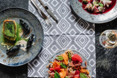 top view of various gourmet dishes and glass of wine on marble table top