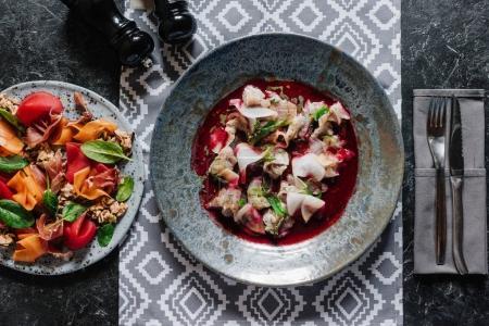 Photo pour Vue de dessus de délicieuse salade aux moules et ceviche gastronomique dans des assiettes - image libre de droit