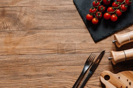 top view of fresh ripe tomatoes on slate board, fork with knife, seasonings in containers and peppercorns on wooden table