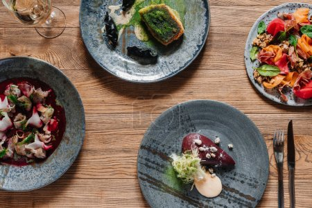 top view of delicious dishes and glass of wine on wooden table
