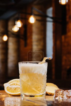 close-up view of glass with ginger nail cocktail on table