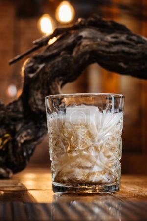close-up view of alcoholic cocktail with cream in glass on wooden table