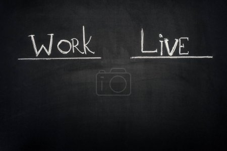 Work and Live underlined inscription on dark chalkboard