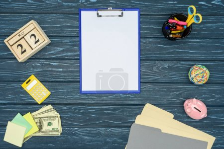 Clipboard with blank paper on blue wooden table with stationery and money
