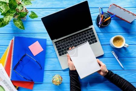Photo pour Vue rapprochée de bloc-notes en mains par ordinateur portable sur une table en bois bleue - image libre de droit