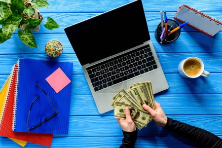 Photo for Business person counting dollars by laptop on blue wooden table with stationery - Royalty Free Image