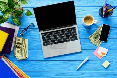 Open laptop on blue wooden table with stationery and money