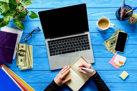 person writing in notebook by laptop on blue wooden table with stationery and money