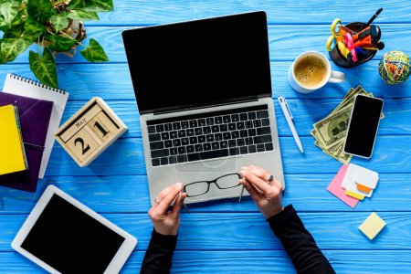 Photo for Hands holding eyeglasses by laptop on blue wooden table with stationery and money - Royalty Free Image