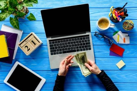 Photo for Business person tying dollars with rubber band by laptop on blue wooden table with stationery - Royalty Free Image