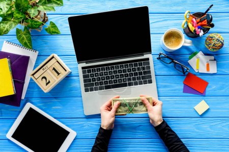 hands holding money by laptop on blue wooden table with stationery