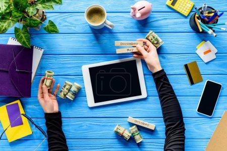 Photo pour Notion de frais de planification avec l'homme d'affaires détenant le calendrier et l'argent sur la table en bois bleue - image libre de droit