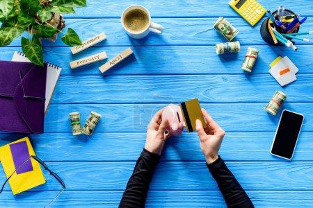 Photo pour Mains tenant tirelire et carte de crédit sur table en bois bleu - image libre de droit