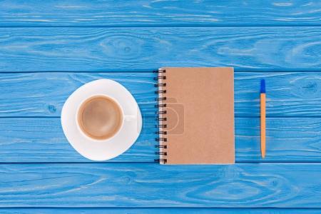 Foto de Vista superior de la pluma, taza de café y libro de texto en tablones de madera azul - Imagen libre de derechos