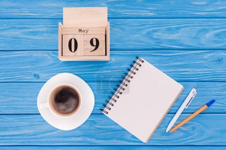 Photo pour Vue du haut du calendrier en bois avec la date du 9 mai, tasse à café, manuel vierge et stylos, concept de jour de la victoire - image libre de droit