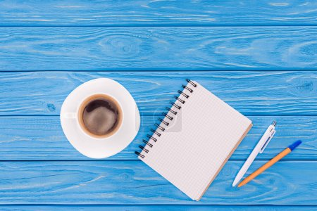 top view of empty textbook, pens and cup of coffee on blue wooden planks