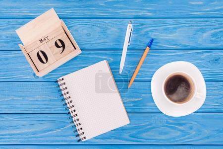 Photo pour Vue du haut du calendrier en bois avec la date du 9 mai, tasse à café, manuel vide et stylos, concept de jour de la victoire - image libre de droit