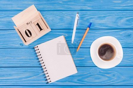 Photo pour Vue de dessus du calendrier en bois avec la date du 1er mai, tasse à café, Manuel vide et stylos, notion de jour de travailleurs internationaux - image libre de droit