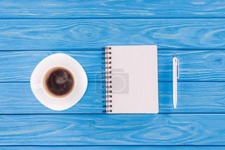 top view of empty textbook, pen and coffee cup on blue wooden planks