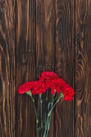 Photo pour Vue de dessus du tas d'oeillets sur des planches de bois - image libre de droit