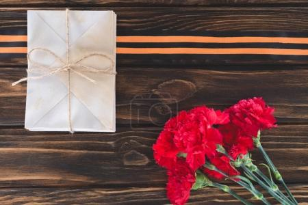 top view of box wrapped by string, carnations and st. george ribbon on wooden surface