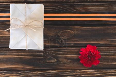 top view of box wrapped by string, carnation and st. george ribbon on wooden planks