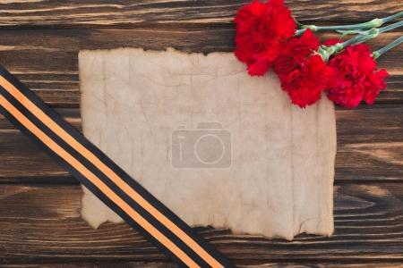 top view of empty old paper, carnations and st. george ribbon on wooden surface