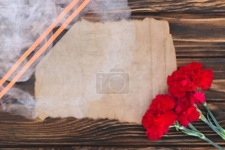 smoke over st. george ribbon, old empty paper and carnations on wooden surface
