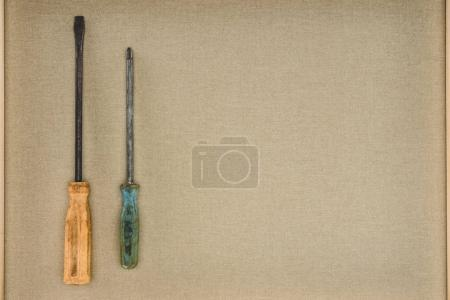 top view of two different screwdrivers on beige background
