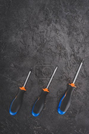 top view of three screwdrivers placed in row on black rustic surface
