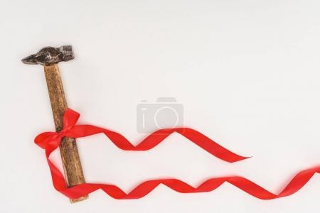 top view of hammer wrapped by red ribbon isolated on white
