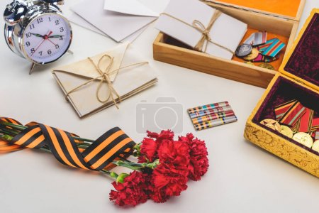 closeup shot of carnations wrapped by st. george ribbon, letters, medals in boxes and alarm clock, victory day concept