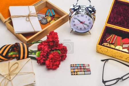 closeup shot of alarm clock, eyeglasses, flowers wrapped by st. george ribbon, letters, medals on gray, victory day concept