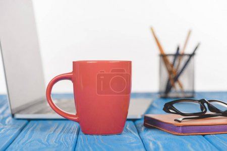 Photo for Closeup shot of red cup, eyeglasses on textbook, laptop and organizer with pens and pencils - Royalty Free Image