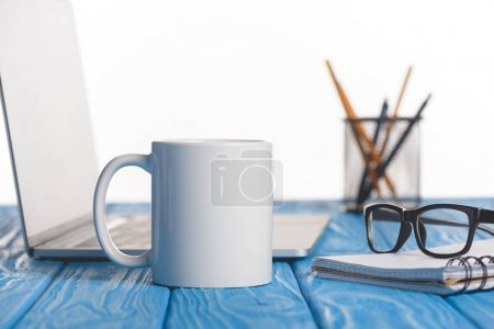 Photo for Closeup shot of cup, eyeglasses on textbook, laptop and organizer with pens and pencils - Royalty Free Image