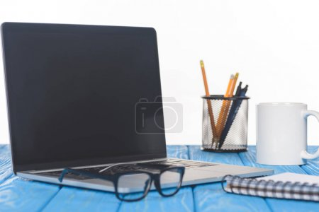 closeup shot of eyeglasses on laptop, textbook, organizer with stationery and mug