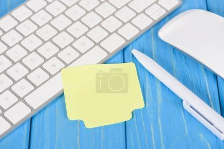 Photo for Closeup shot of empty note paper, pen, computer keyboard and mouse on blue wooden surface - Royalty Free Image