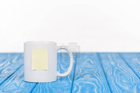 closeup shot of cup with empty note paper on wooden blue surface