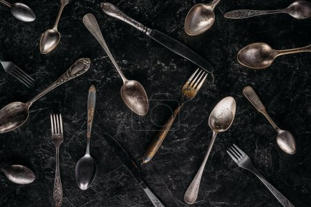 Vintage spoons and forks with knives on dark background